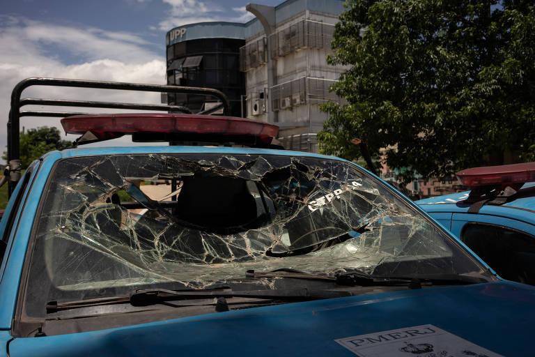 """Em primeiro plano, viatura de policia com para-brisa quebrado em frente à prédio com letreiro """"UPP""""."""