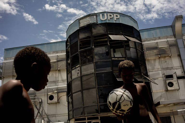 """Duas crianças negras e sem camisa jogam com uma bola de futebol em frente à prédio com letreiro """"UPP""""."""