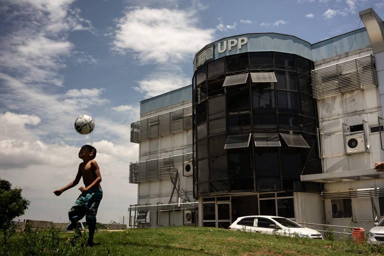 """Menino negro e sem camisa joga bola em frente à prédio com letreiro """"UPP""""."""