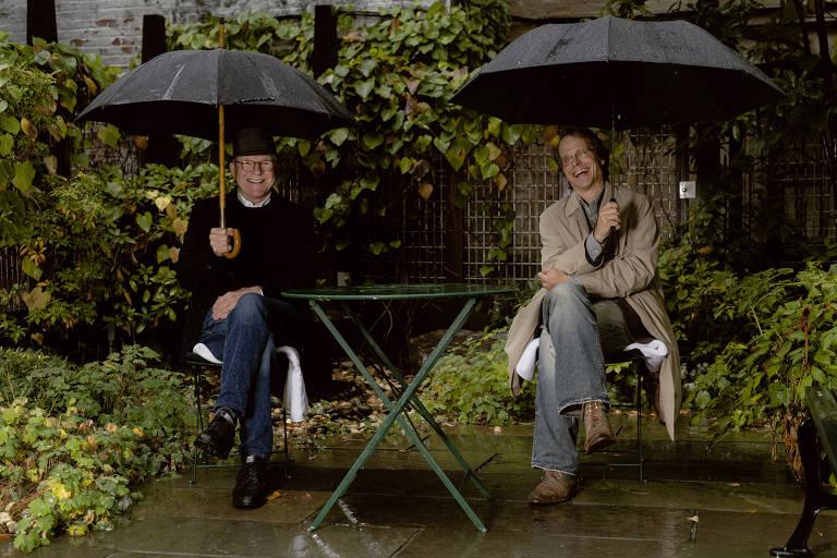 Dois homens sentados lado a lado seguram guarda-chuva e sorriem