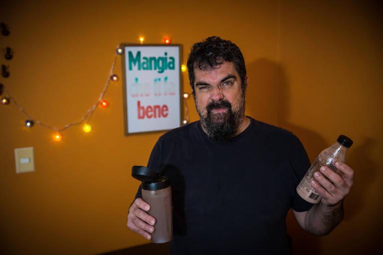 Em sua casa, Marcos segura duas garrafas do produto e olha para a câmera de forma desconfiada