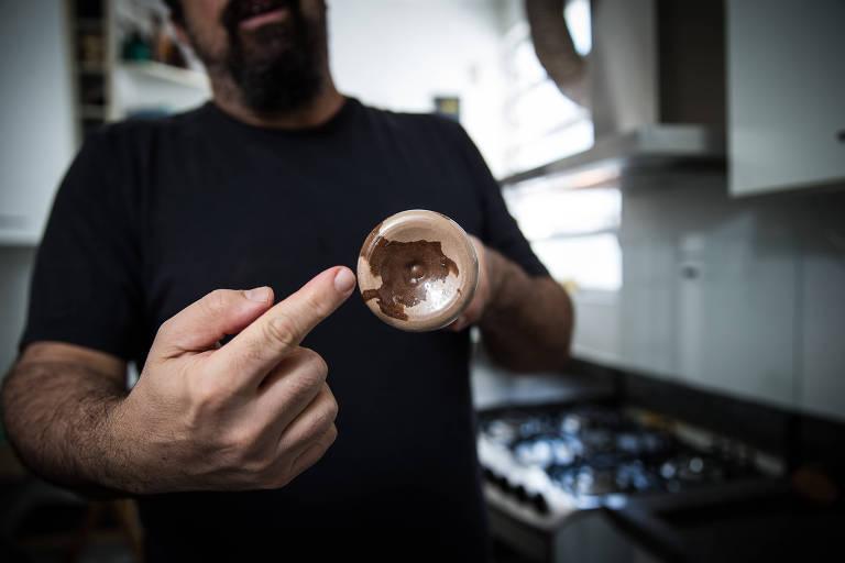 Marcos aponta para o fundo da garrafa, onde pelotas do pó não se dissolveram completamente