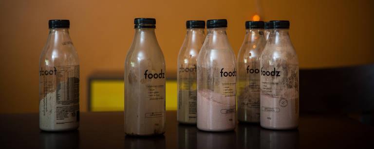 Seis garrafas transparentes com o pó ainda não diluído em água