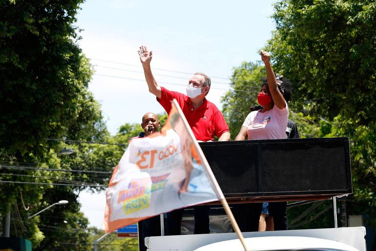 Homem de camisa vermelha está em cima de um trio elétrico com bandeira do PT