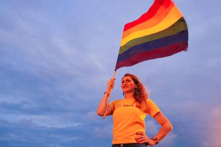 Mulher trans segura bandeira com o arco-íris LGBTQIA+