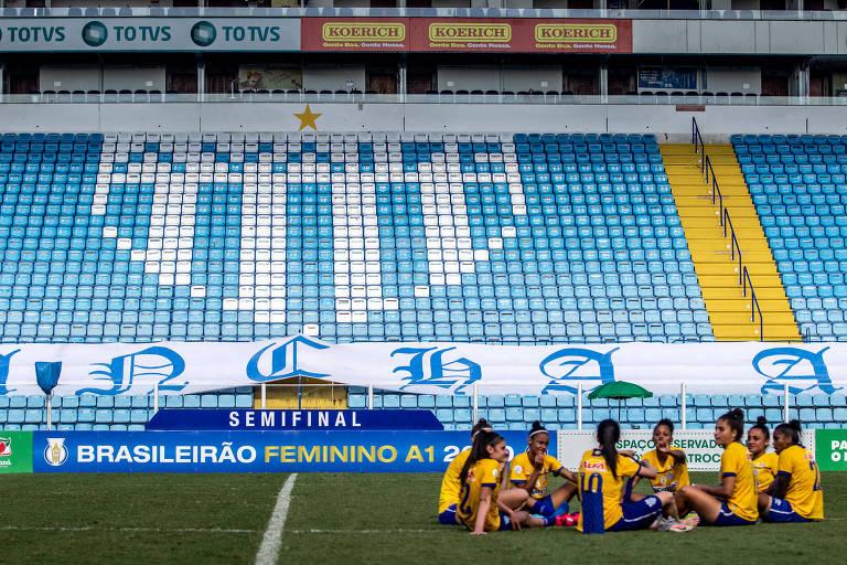 Jogadoras sentadas no gramado da Ressacada