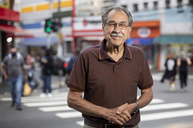 Um homem idoso de óculos parado numa esquina diante de uma faixa de pedestre e pessoas caminhando ao fundo