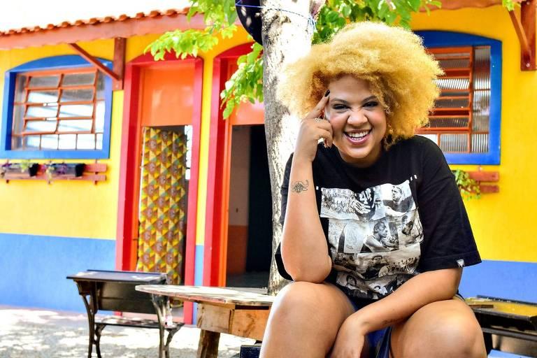 Mulher negra de cabelos louros posa para a foto sentada e sorridente