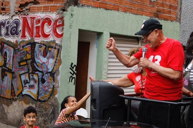 Um homem de camisa vermelha e boné falando ao microfone do alto de um caminhão