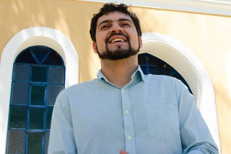 Homem de camisa azul sorri com prédio amarelo com detalhes em branco nas janelas ao fundo