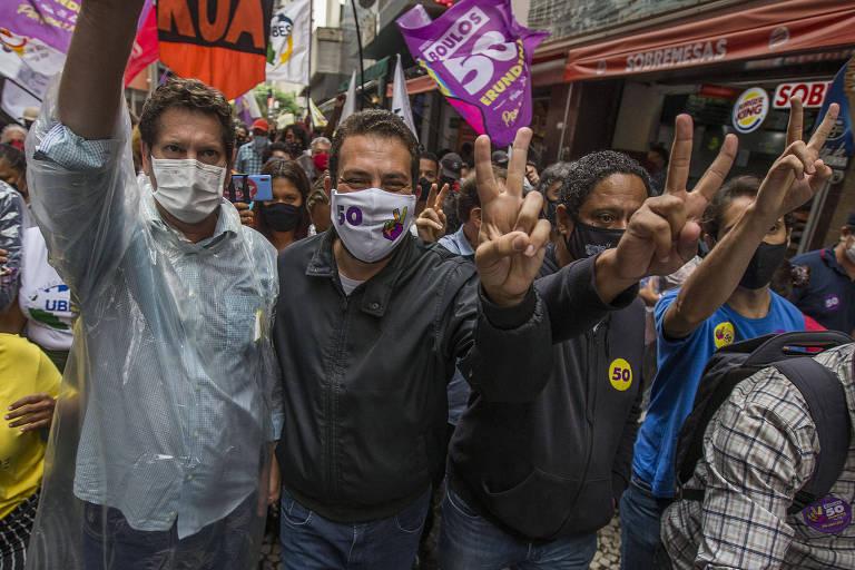 Guilherme Boulos (PSOL) faz caminhada com apoiadores no centro de São Paulo ao lado dos derrotados no primeiro turno Jilmar Tatto (PT) e Orlando Silva (PC do B)