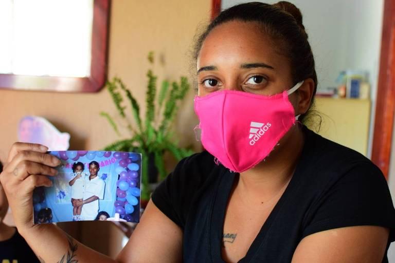 Thais Freitas, 22, filha mais velha de Beto Freitas. Ela segura uma foto em que aparece quando criança no colo do pai