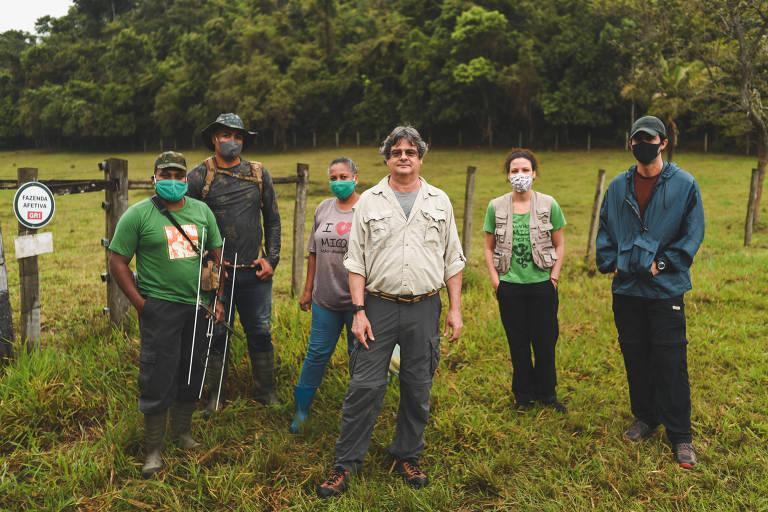 Seis pessoas posam para a câmera em um pasto com uma mata ao fundo