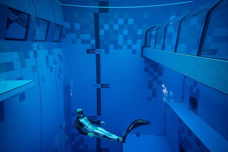 Mergulhador nada em grande piscina que tem um túnel de vidro no meio dela