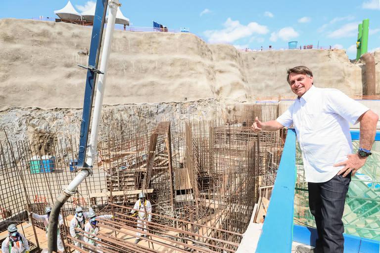 obra com funcionários que vestem branco ao lado direito da imagem; ao lado esquerdo, Bolsonaro sorri e faz um sinal de positivo com a mão