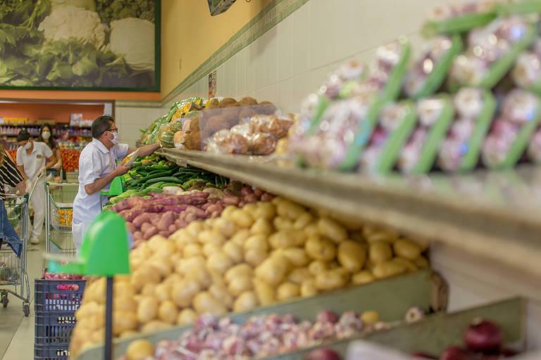 Imagem mostra, ao fundo, homem escolhendo legumes em um supermercado; na frente, um cesto de batatas