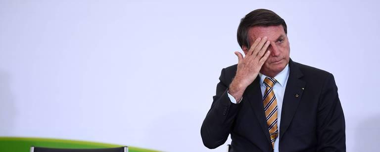 Jair Bolsonaro senta ao lado direito, com uma cadeira vazia ao lado esquerdo; o presidente coça o olho