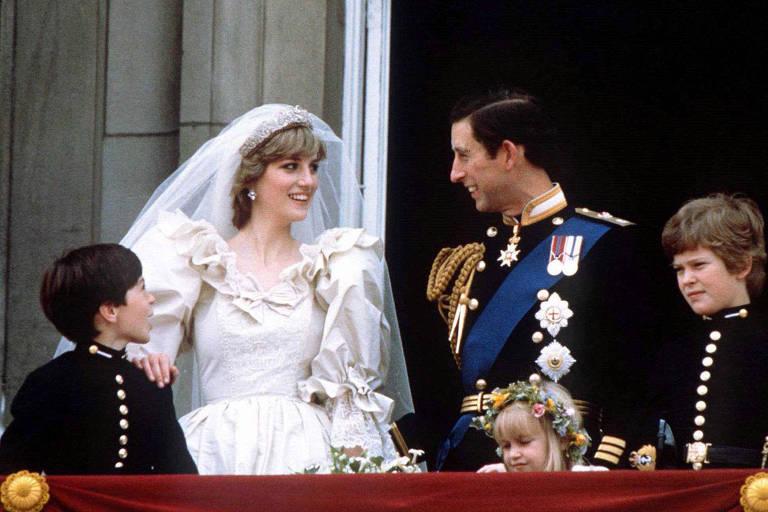 Mulher branca loira vestida de noiva ao lado de homem branco moreno vestido de noivo