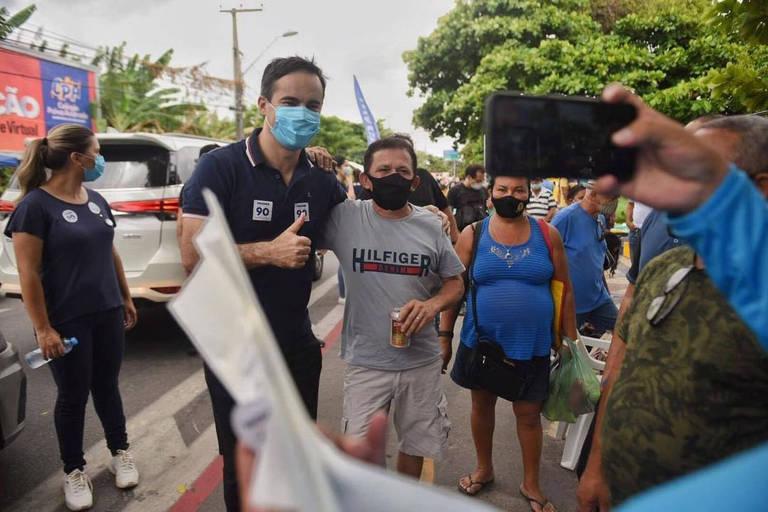 Homem de máscara tira fotos com pessoas na rua
