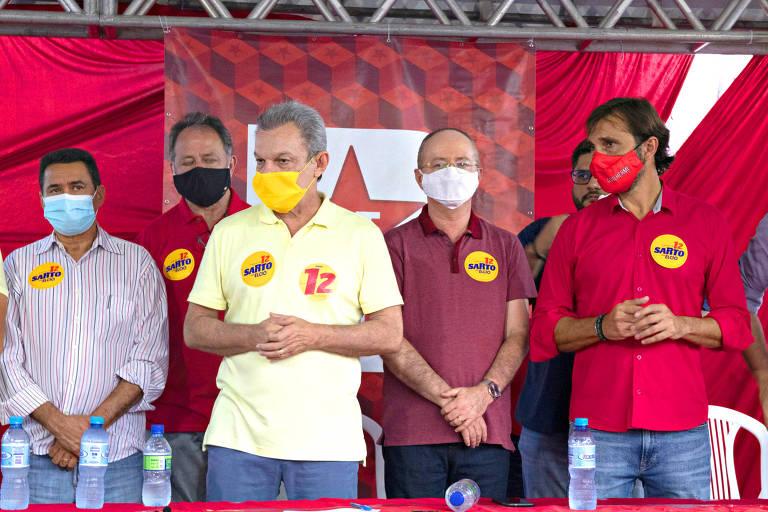 homem de máscara amarela em palanque com outros homens de camisa vermelha
