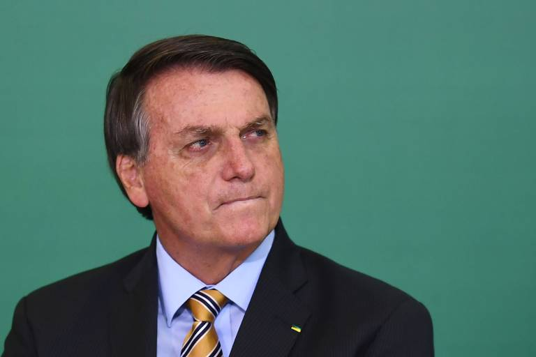 O presidente do Brasil, Jair Bolsonaro, encolhe os lábios e parece olhar longe nesta foto em que só ele aparecem de terno escurro e gravata em tom amarelo. O fundo é verde.