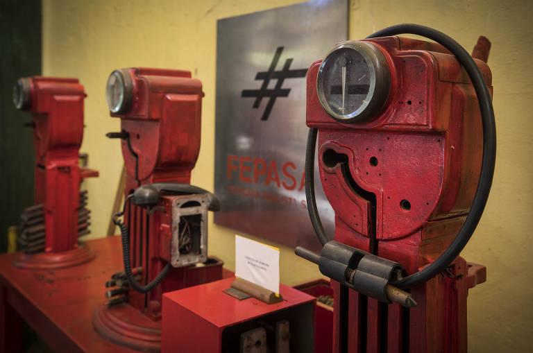 Equipamentos vermelhos, antigos, expostos em museu, com logo escrito Fepasa ao fundo
