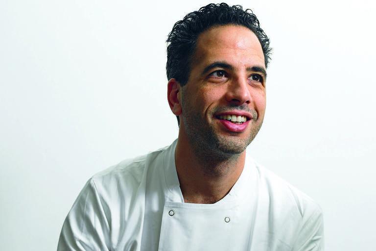 O chef sorri olhando para o alto, sentado num banco