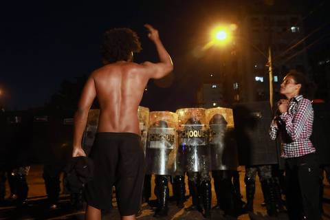 A black man confronts riot police as a black woman prays during a protest against the death of Joao Alberto Silveira Freitas in Porto Alegre, Brazil on November 23, 2020. - The death of a black man beaten by white security agents in a supermarket belonging to the Carrefour group in Porto Alegre on Thursday night unleashed a wave of indignation in Brazil. (Photo by SILVIO AVILA / AFP)