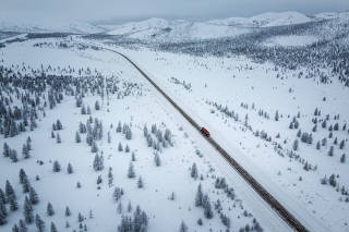 A lone truck traverses the Kolyma Highway, the notorious 'road of bones' in Russia's Far East, Nov. 23, 2019. (Emile Ducke/The New York Times)