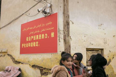 FILE -- Cameras watching a street in Hotan, a city in the western Chinese region of Xinjiang, Dec. 11, 2019. The poster warns that Òcriminal forcesÓ will be severely dealt with. Such surveillance is commonplace in the region. (Giulia Marchi/The New York Times) ORG XMIT: XNYT62