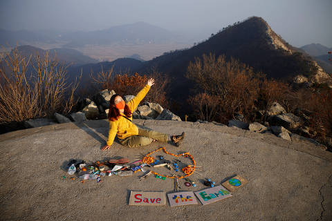 Kim Kang-Eun, an artist who leads Clean Hikers, poses artwork made from litter collected by members of Clean Hikers during their hikes, on the peak of a mountain in Incheon, South Korea, November 16, 2020. Picture taken November 16, 2020. REUTERS/Kim Hong-Ji ORG XMIT: HFS-PPPKHJ01