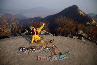 Kim Kang-Eun, an artist who leads Clean Hikers, poses artwork made from litter collected by members of Clean Hikers during their hikes, on the peak of a mountain in Incheon, South Korea
