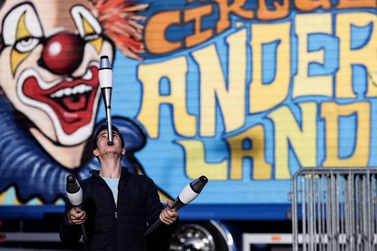 À frente de um muro com um palhaço pintado, uma jovem equilibra malabares na boca, em treino no estacionamento, enquanto seu circo está parado devido às restrições impostas pela pandemia, em Gembloux, na Bélgica