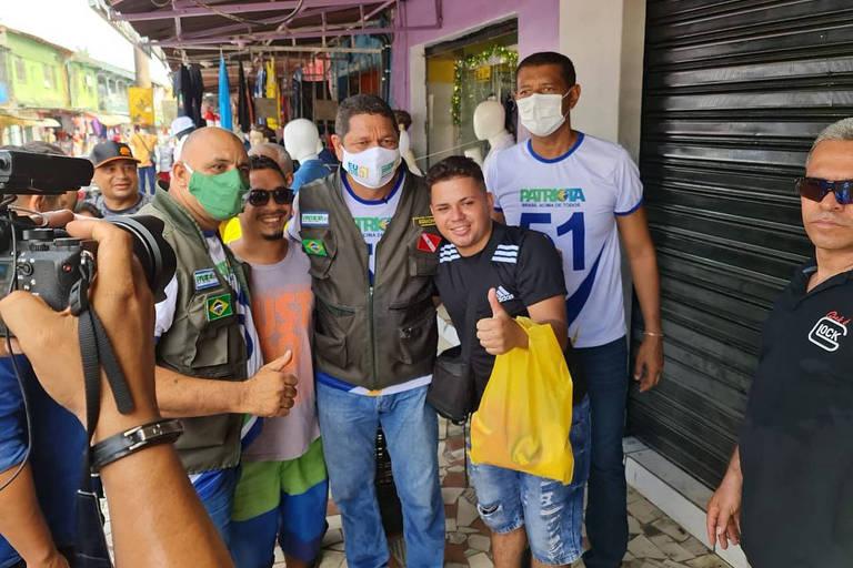 Homem de máscara e colete abraça na rua eleitores de máscara