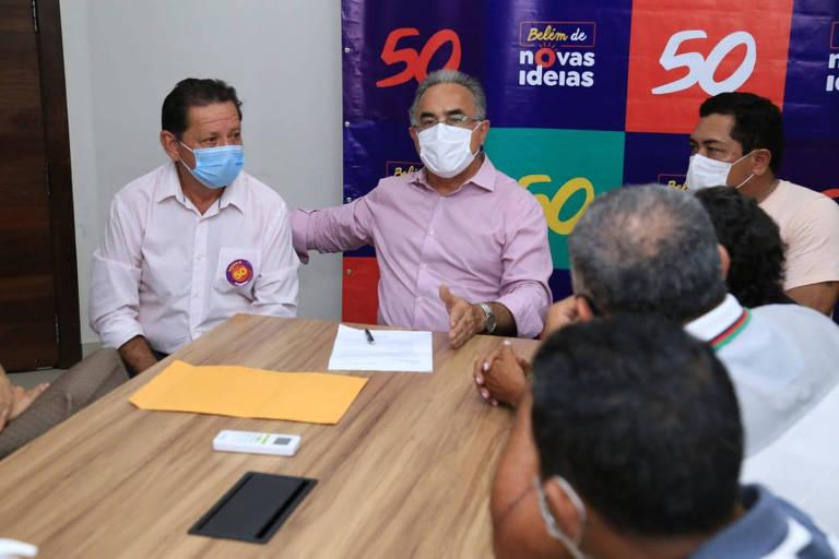 Homem de máscara está sentado em mesa com apoiadores de campanha, também de máscara