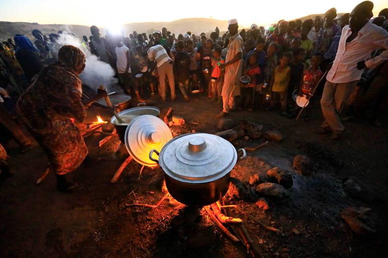 Refugiados etíopes que fugiram do conflito no Tigré aguardam por refeição em campo na fronteira do país com o Sudão