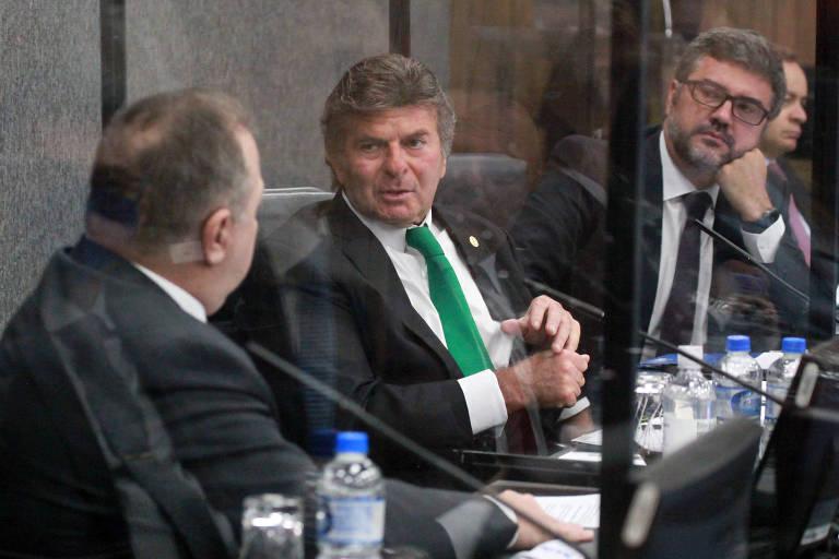 O ministro Luiz Fux, presidente do CNJ, em audiência no conselho; vemos o ministro sentado a uma mesa com microfones, ladeado por outros dois homens; ele está no centro da foto e usa uma gravata verde
