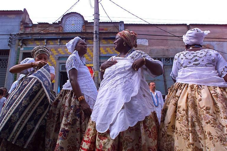 Mulheres em ritual de candomblé para espantar os maus espíritos durante a retomada das escavações do Cemitério dos Pretos Novos, na Gamboa, em 2001; o cemitério de escravos recém-chegados da África foi descoberto em 1996, quando os proprietários da casa resolveram cavar o terreno durante uma reforma. Veem-se quatro mulheres vestidas como baianas, com saias rodadas estampadas, blusas e faixas brancas e turbantes; ao fundo, casinhas coloridas