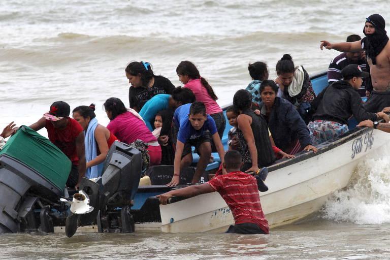 Pessoas desembarcam de embarcação pequena em praia