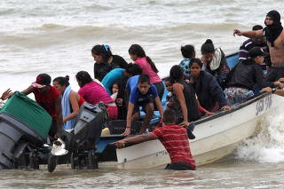 Venezuelan migrants, who were recently deported, arrive at shore on Los Iros Beach after their return to the island, in Erin