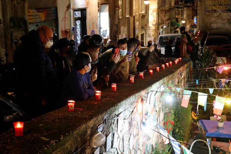 Fãs se reúnem próximo a uma mureta, onde há uma sequência de velas acesas
