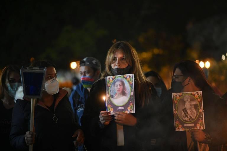 Manifestantes carregam cartazes e velas durante vigília na Cidade da Guatemala em memória de mulher assassinada