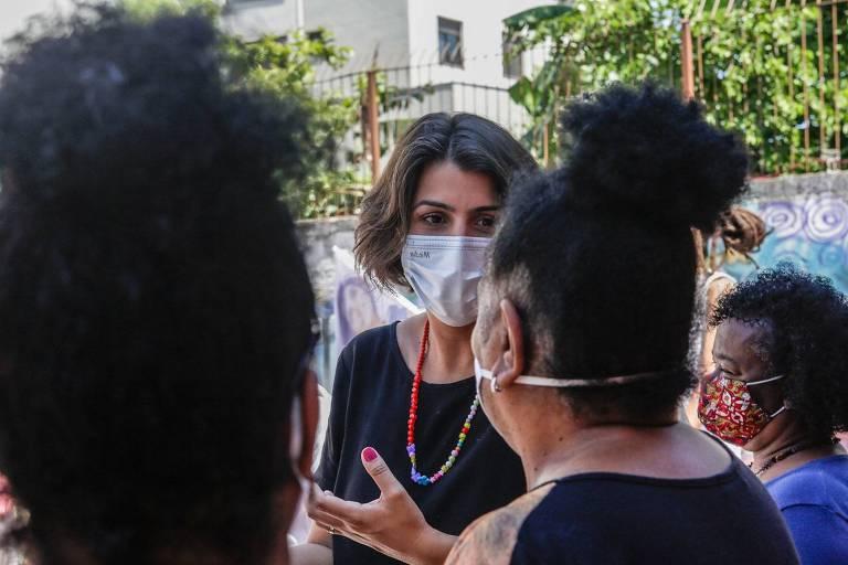 Mulher de máscara conversa com outra mulher, de costas