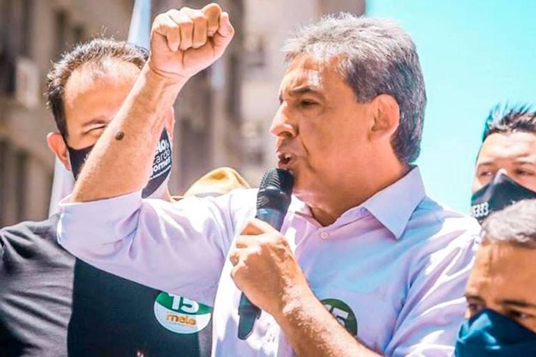 Homem de camisa social com microfone na mão discursa observado por outras pessoas