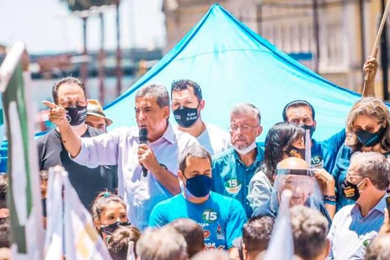 Homem discursa com microfone rodeado de pessoas