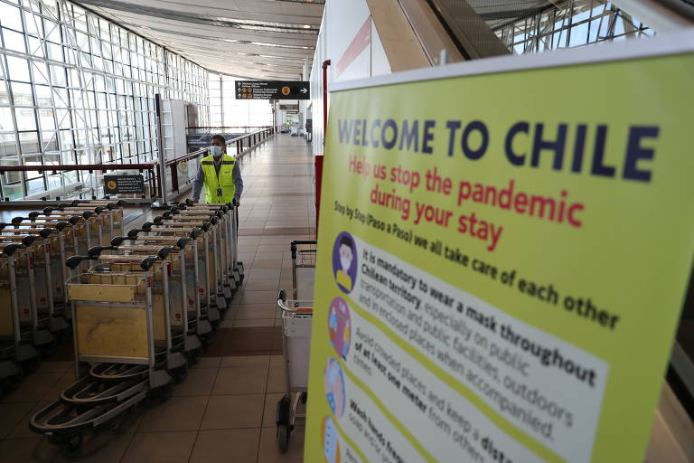 Funcionário empurra carrinhos perto de banner com orientações contra a Covid-19 no Aeroporto Internacional de Santiago, no Chile,  na segunda (23), dia em que o país voltou a aceitar turistas estrangeiros