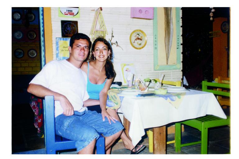 Casal aparece sentado sorrindo para foto; ele veste camiseta branca e bermuda jeans e ela, regata azul e bermuda azuis