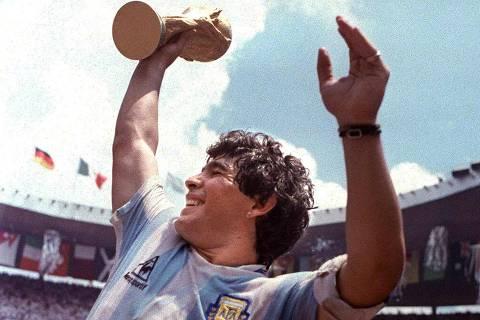 Futebol - Copa do Mundo do México, 1986: Argentina 3x2 Alemanha Ocidental: o jogador Maradona, capitão da seleção argentina, ergue a taça para festejar a Copa do Mundo na vitória sobre a Alemanha Ocidental, no estádio Azteca, na cidade do México. *** El futbolista argentino Diego Maradona levanta el trofeo de la Copa Mundial de Futbol, el 29 de junio de 1986 en Ciudad de Mexico. El Comite Ejecutivo de la Asociacion del Futbol Argentino (AFA) aprobo al noche del 25 de setiembre de 2001 no utilizar mas desde noviembre la camiseta diez (10) de cualquier seleccionado de balompie local, como homenaje al retirado ex jugador Maradona (de 40 anos), segun anuncio la prensa en el 25 de setiembre. AFP PHOTO *** (Imagem retransmitida) (FILE) Argentina's soccer star team captain Diego Maradona brandishes the World Cup won by his team after a 3-2 victory over West Germany 29 June 1986 at the Azteca stadium in Mexico City. Argentinian football legend Diego Maradona was named coach of the national team on October 28, 2008 in Buenos Aires, according to 1986 World Cup winning coach Carlos Bilardo, after he came out of a meeting with Argentinian Football Association president Julio Grondona. ***