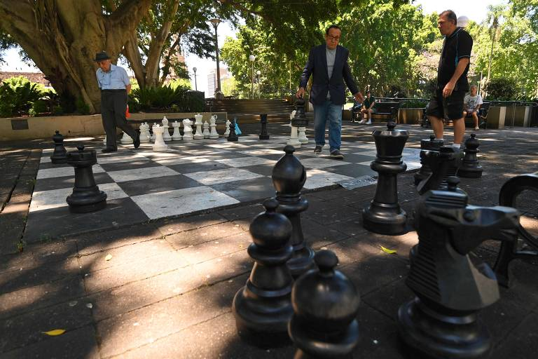 Três pessoas ao redor de tabuleiro de xadrez pintado no chão com peças gigantes