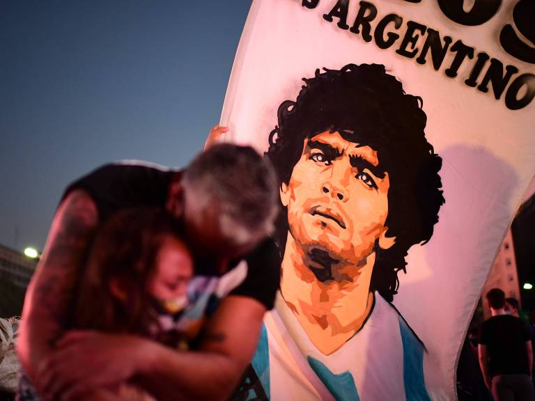 Um pai e sua filha, fãs da lenda do futebol argentino Diego Maradona, choram ao se reunirem no Obelisco de Buenos Aires para prestar homenagem ao ídolo
